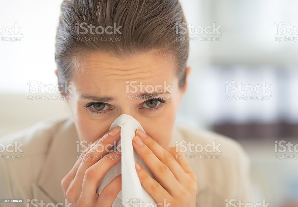 portrait of business woman in office blowing nose royalty-free stock photo