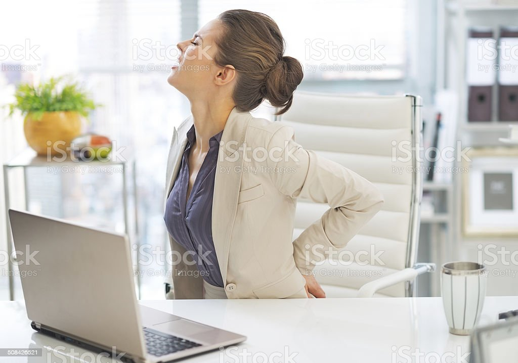 portrait of business woman with back pain in office stock photo