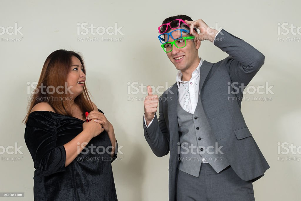 Portrait of businessman giving thumbs up to woman stock photo