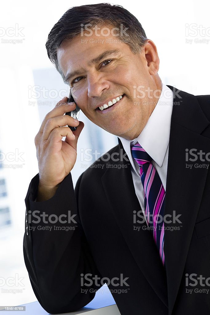 Portrait of businessman on mobile phone looking at camera stock photo