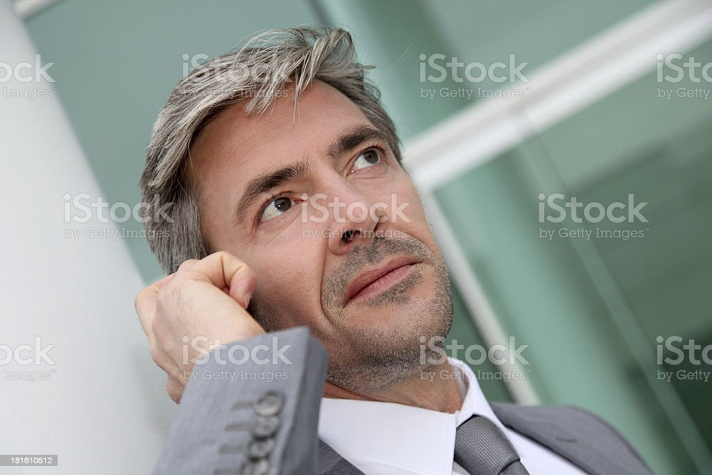 Portrait of businessman outdoors talking on smartphone royalty-free stock photo