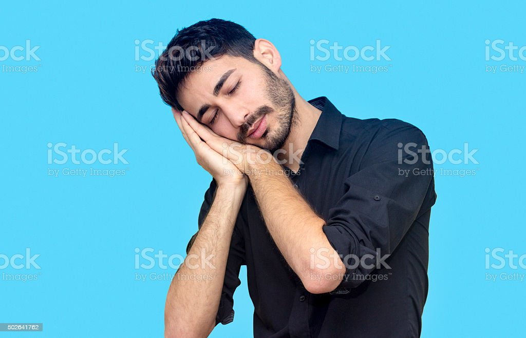 Portrait of businessman sleeping on his hands stock photo