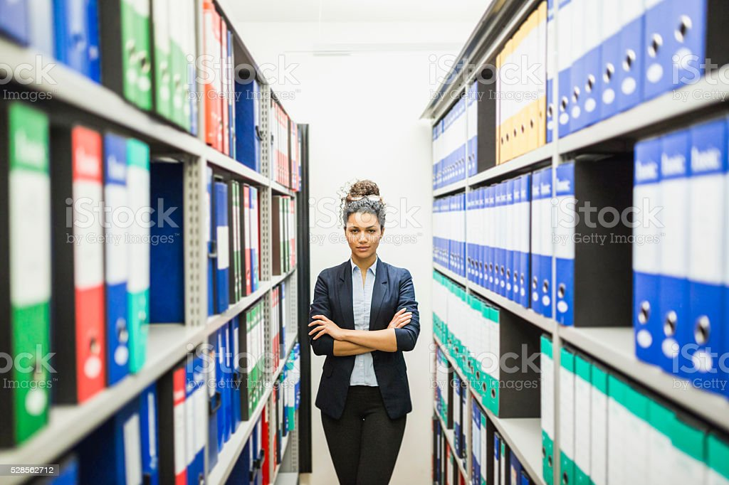 Portrait of businesswoman in basement paper archive stock photo