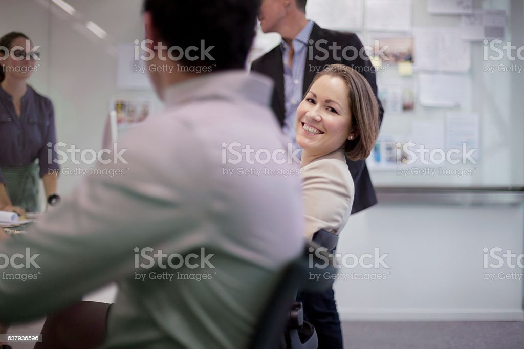 Portrait of businesswoman in busy planning meeting with colleagues stock photo