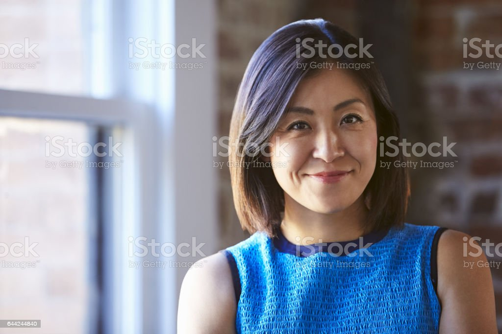 Portrait Of Businesswoman In Office Standing By Window stock photo