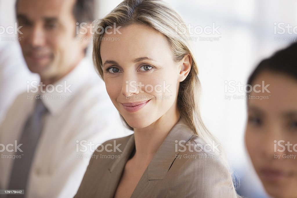 Portrait of businesswoman with colleagues in conference room royalty-free stock photo