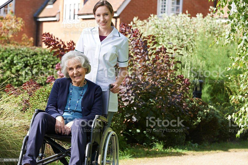 Portrait Of Carer Pushing Senior Woman In Wheelchair stock photo