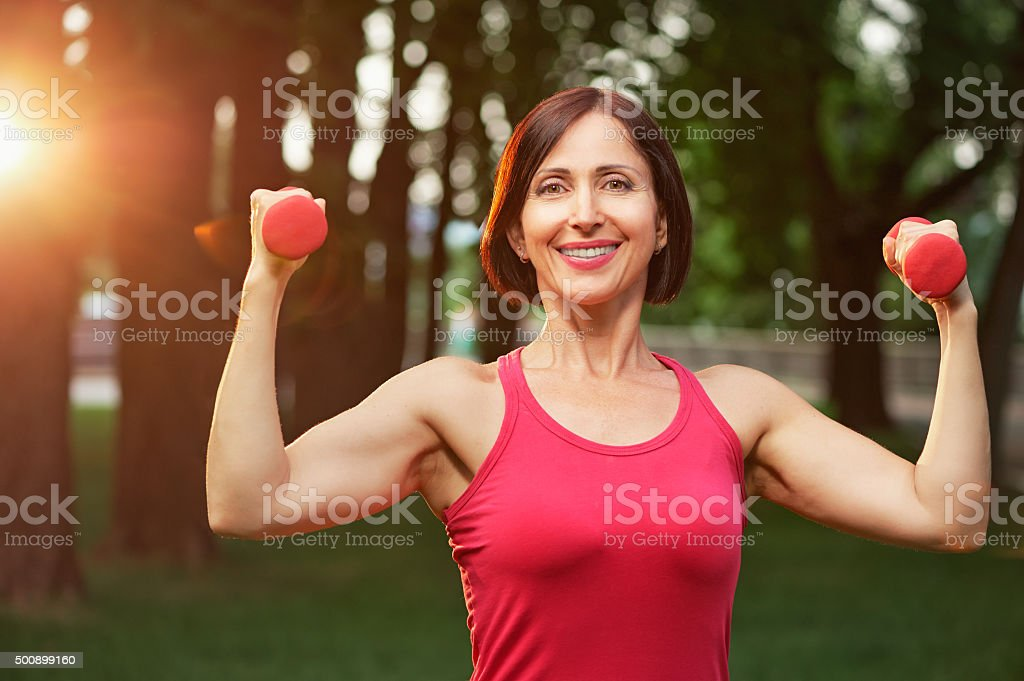Portrait of cheerful aged woman in fitness wear exercising with stock photo