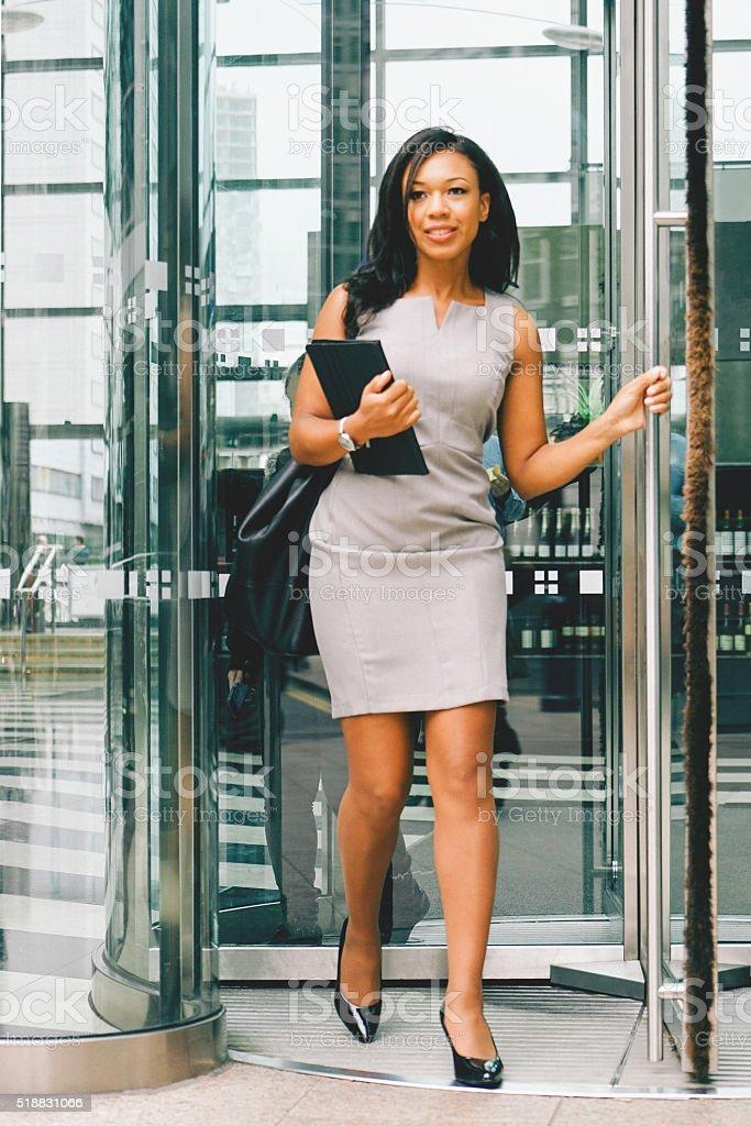 Portrait Of Cheerful Businesswoman Walking Through Revolving Doors stock photo