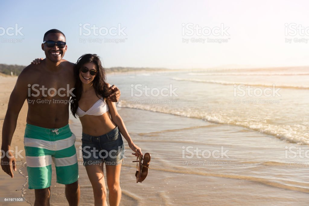 Portrait of cheerful couple standing at beach stock photo