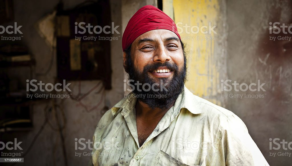 Portrait of Cheerful Indian Sikh Mechanic Manual Worker stock photo