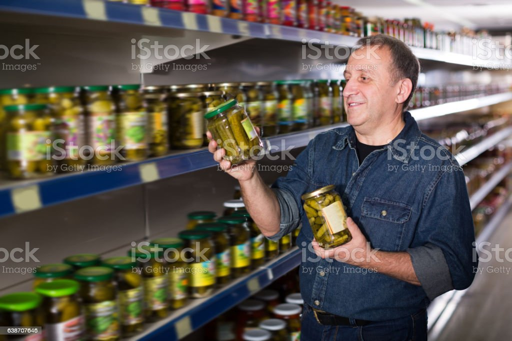 Portrait of cheerful man buying a cucumbers stock photo