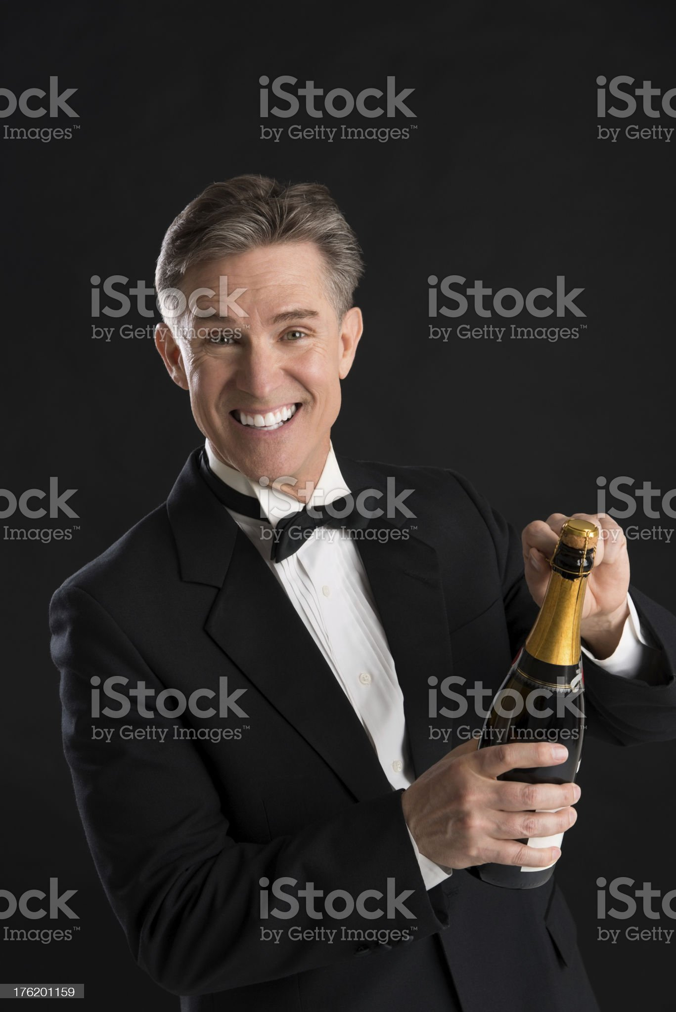Portrait Of Cheerful Man In Tuxedo Opening Champagne Bottle royalty-free stock photo