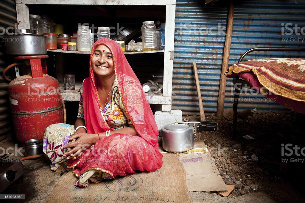 Portrait of Cheerful Rajasthani Indian female sitting in her Kitchen stock photo
