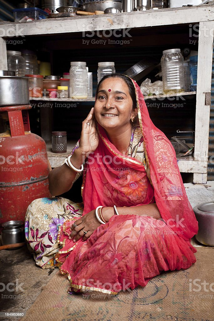 Portrait of Cheerful Rajasthani Indian woman sitting in her Kitchen stock photo