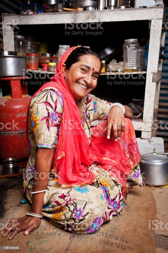 Portrait of Cheerful Rural Rajasthani Indian woman sitting in Kitchen stock photo