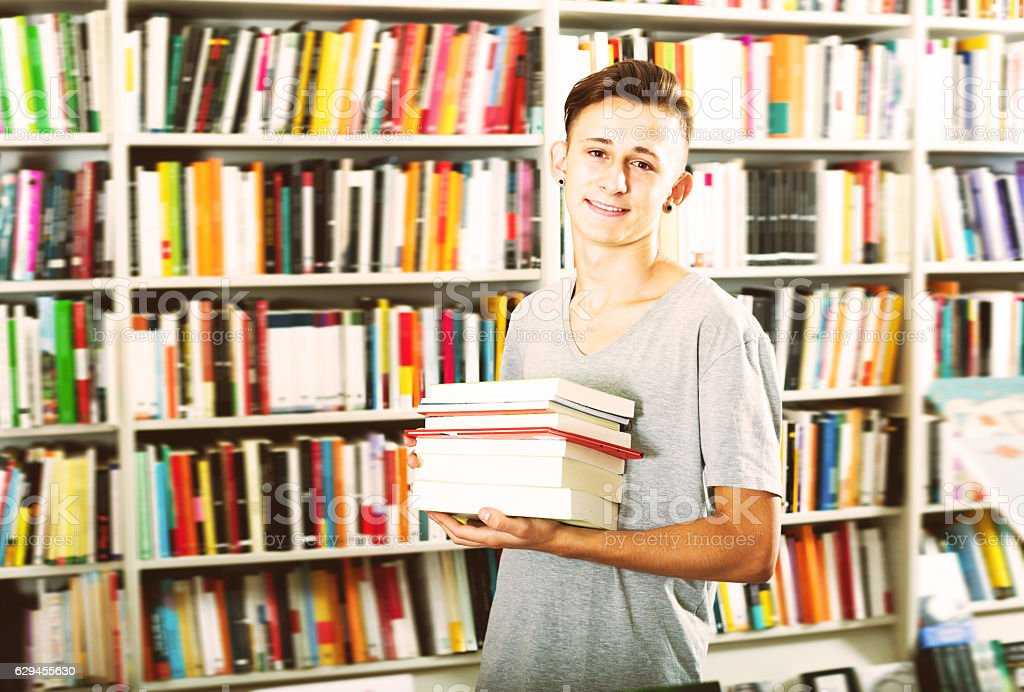 Portrait of cheerful teenager boy with book pile stock photo