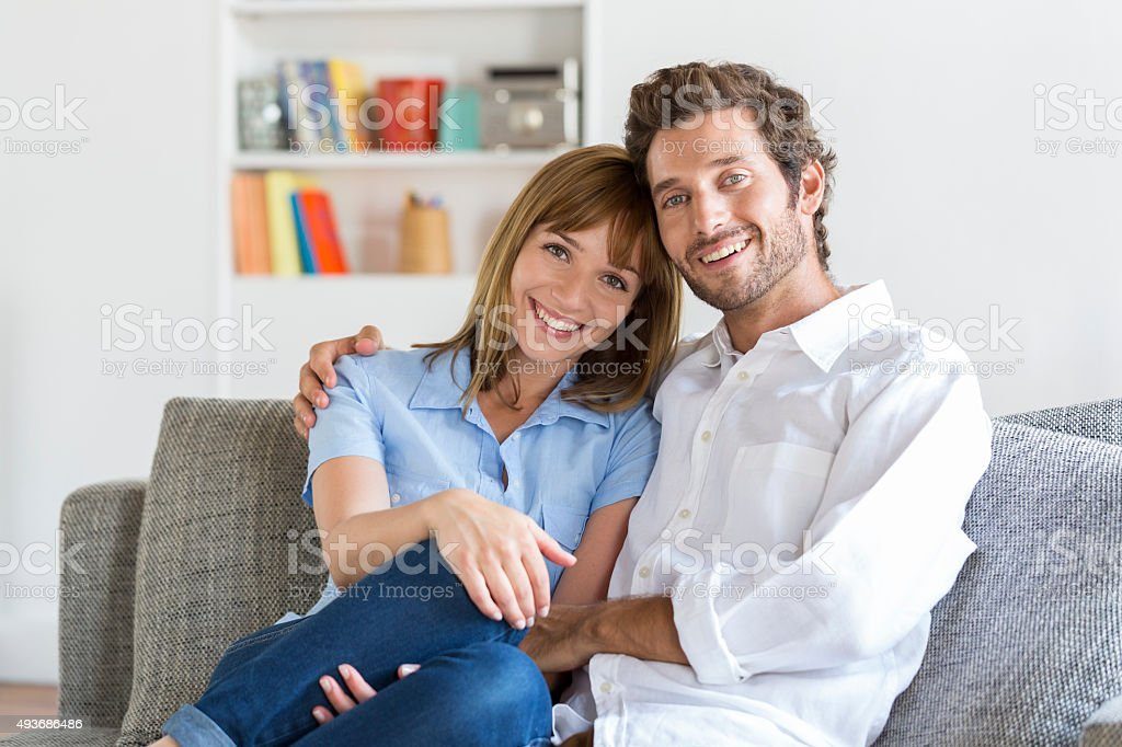 Portrait of cheerful thirty year old couple sitting on sofa stock photo