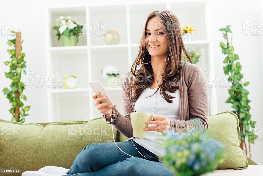 Portrait of cheerful woman drinking coffee and listening to music stock photo