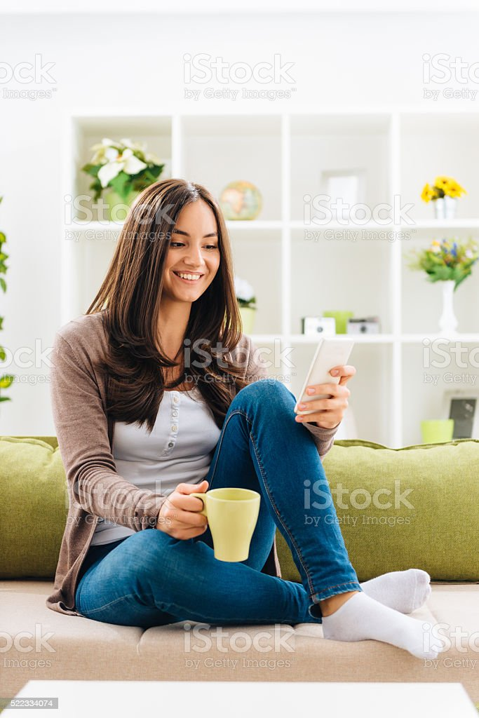 Portrait of cheerful woman drinking coffee and using smartphone stock photo