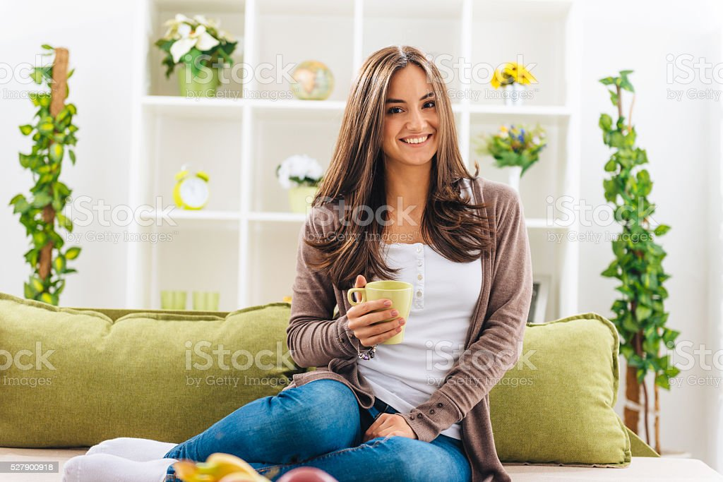 Portrait of cheerful woman drinking coffee at home and smiling stock photo