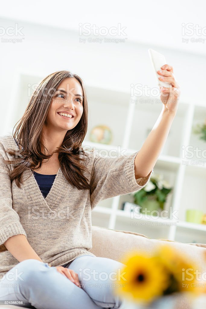 Portrait of cheerful woman taking selfie shot and smiling stock photo