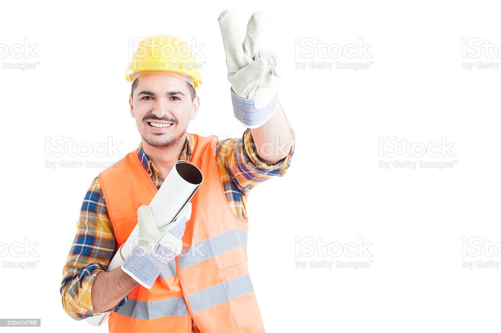 Portrait of cheerful young engineer making peace or victory gest stock photo