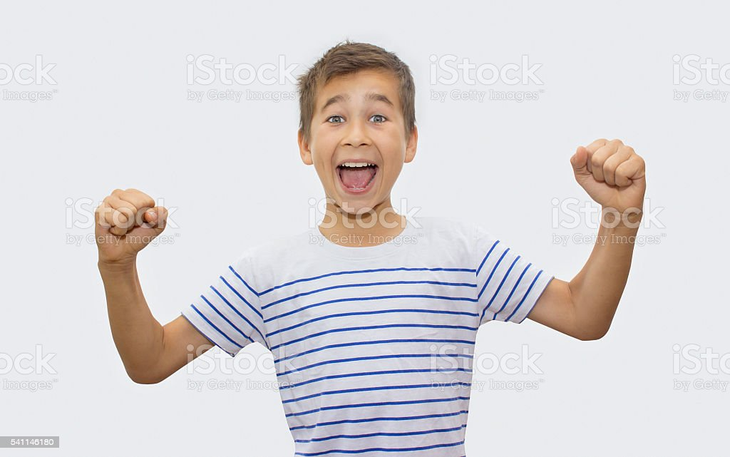 Portrait of cheering boy over gray background stock photo