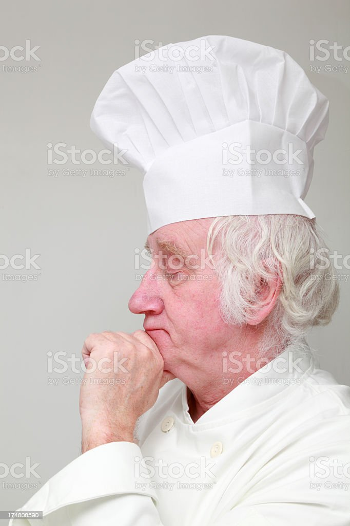 portrait of chef deep in thought on plain background royalty-free stock photo