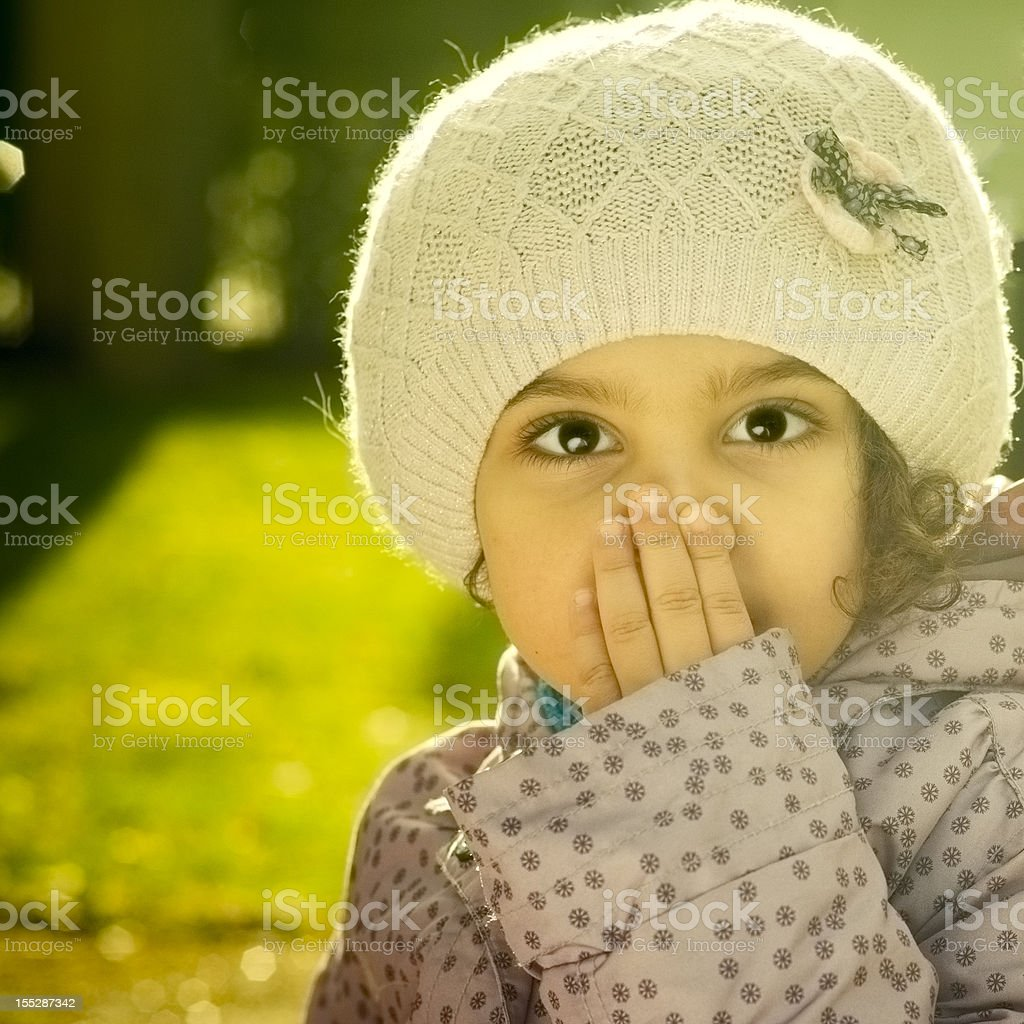 Portrait of Child (4-5) Covering Mouth with Her Hand stock photo