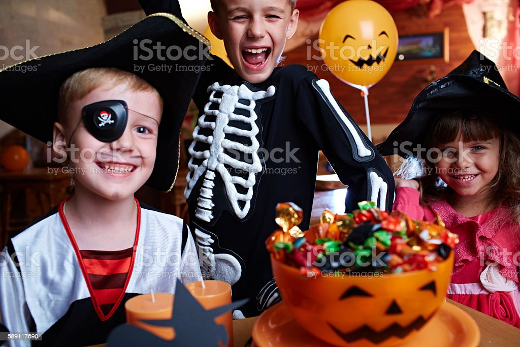 Portrait of children with candy bowl at Halloween party stock photo