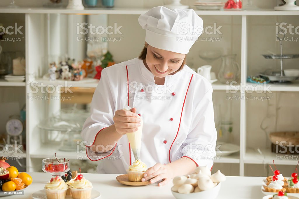 Portrait of confectioner topping a cupcake with cream stock photo