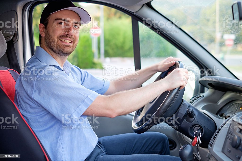 Portrait of confidence express courier driving his delivery van stock photo