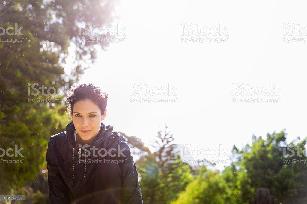 Portrait of confident athlete exercising at park stock photo