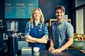 Portrait of confident baristas standing at cafe counter