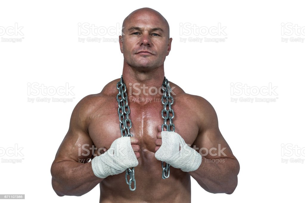 Portrait of confident bodybuilder holding chain around neck royalty-free stock photo