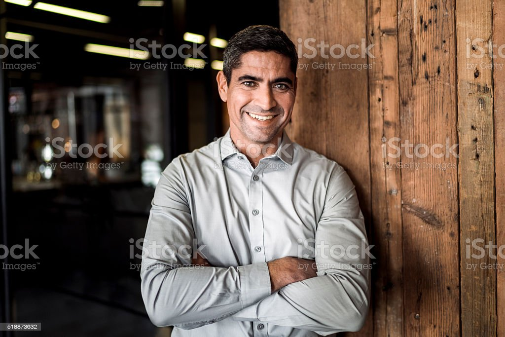 Portrait of confident businessman against wooden wall stock photo