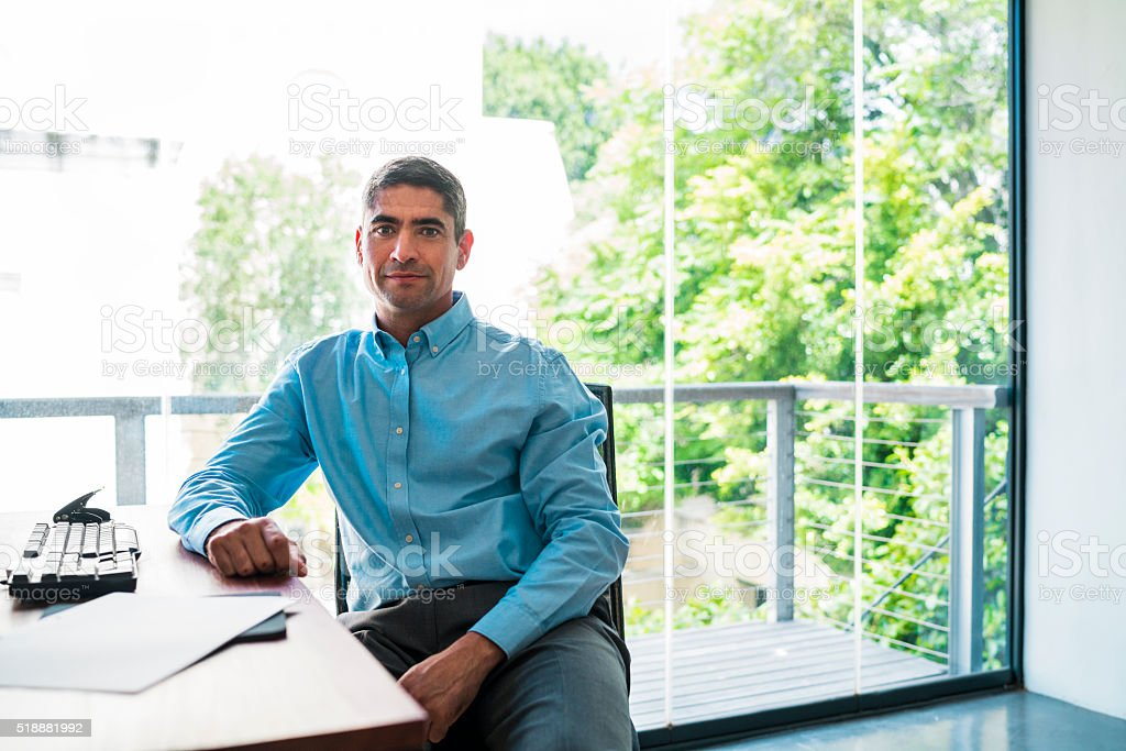 Portrait of confident businessman sitting at office desk stock photo