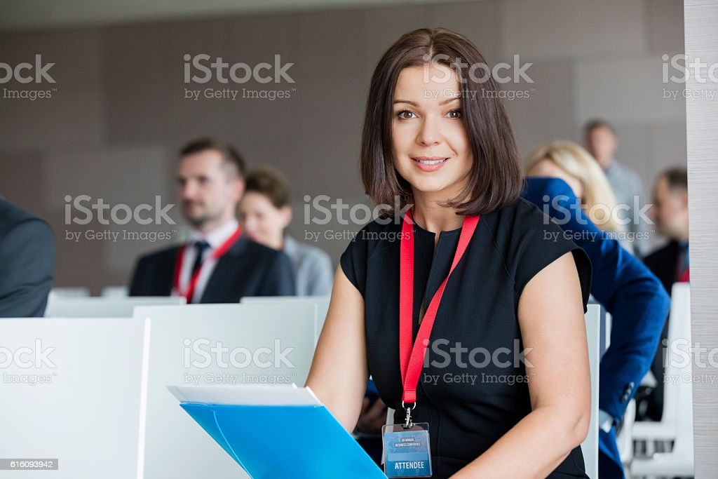 Portrait of confident businesswoman sitting in seminar hall stock photo