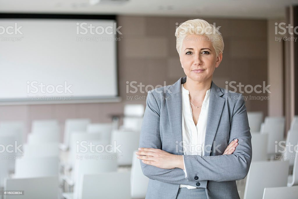 Portrait of confident businesswoman standing arms crossed in seminar hall stock photo