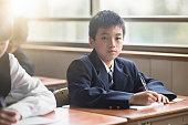 Portrait of confident high school boy in classroom
