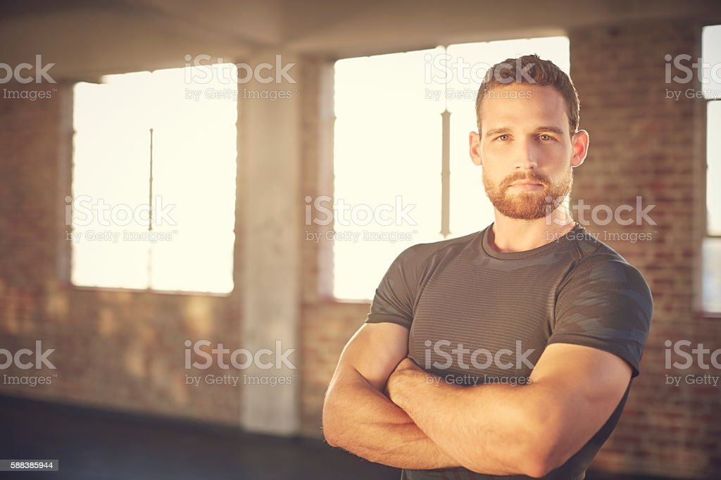 Portrait of confident muscular man standing arms crossed in gym stock photo