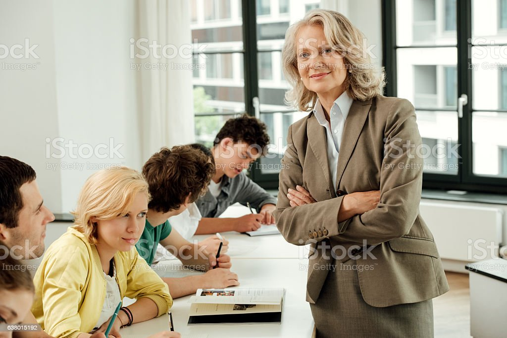 Portrait of confident professor with university students in classroom stock photo