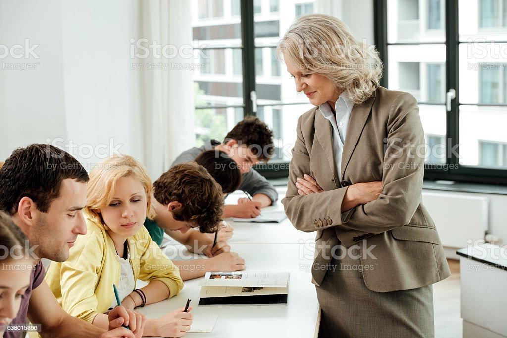 Portrait of confident professor with university students in classroom stock photo