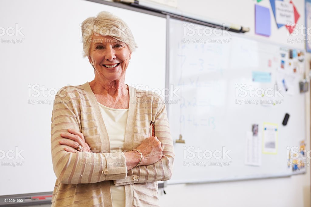Portrait of confident senior female teacher in classroom stock photo