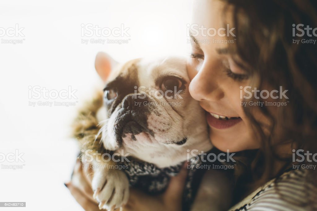 Portrait of confident woman carrying french bulldog stock photo