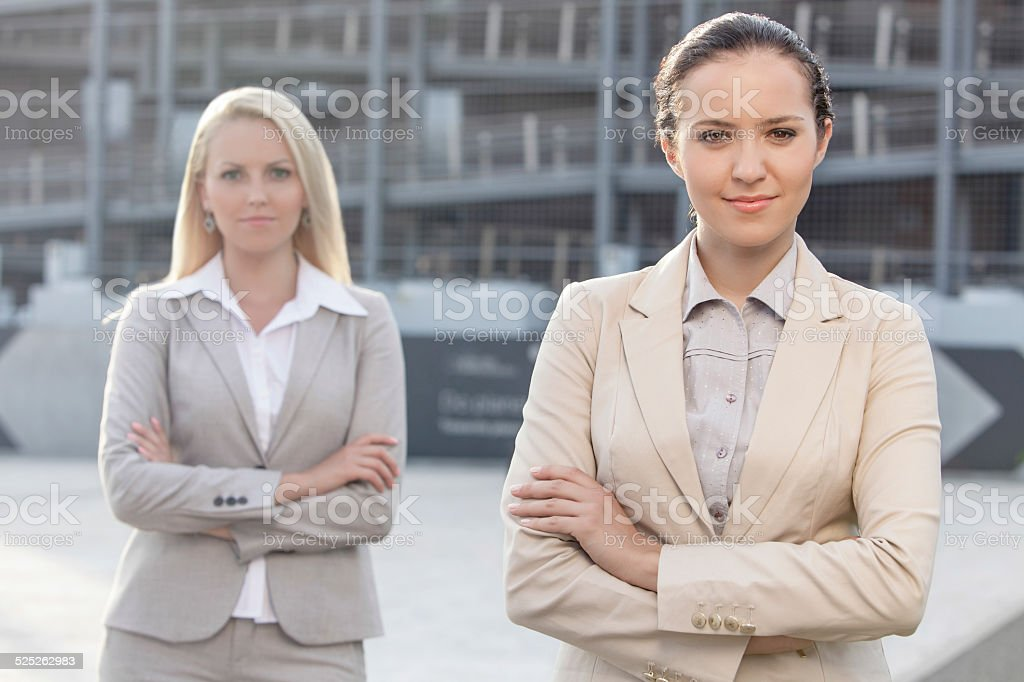 Portrait of confident young businesswomen standing arms crossed outdoors stock photo