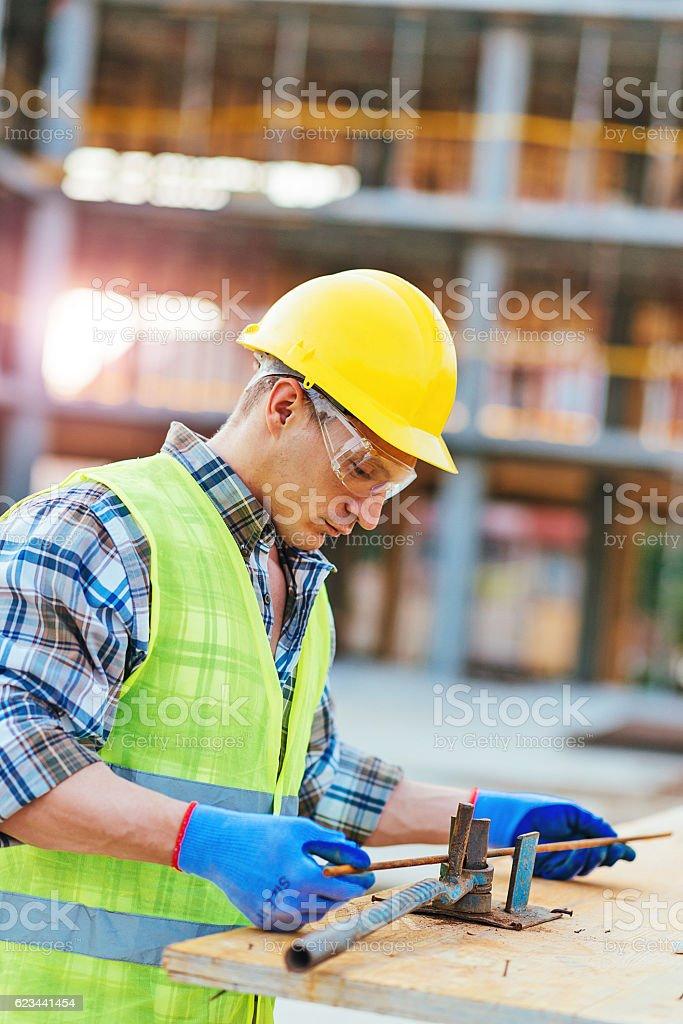 Portrait of construction worker bending steel armature rods stock photo