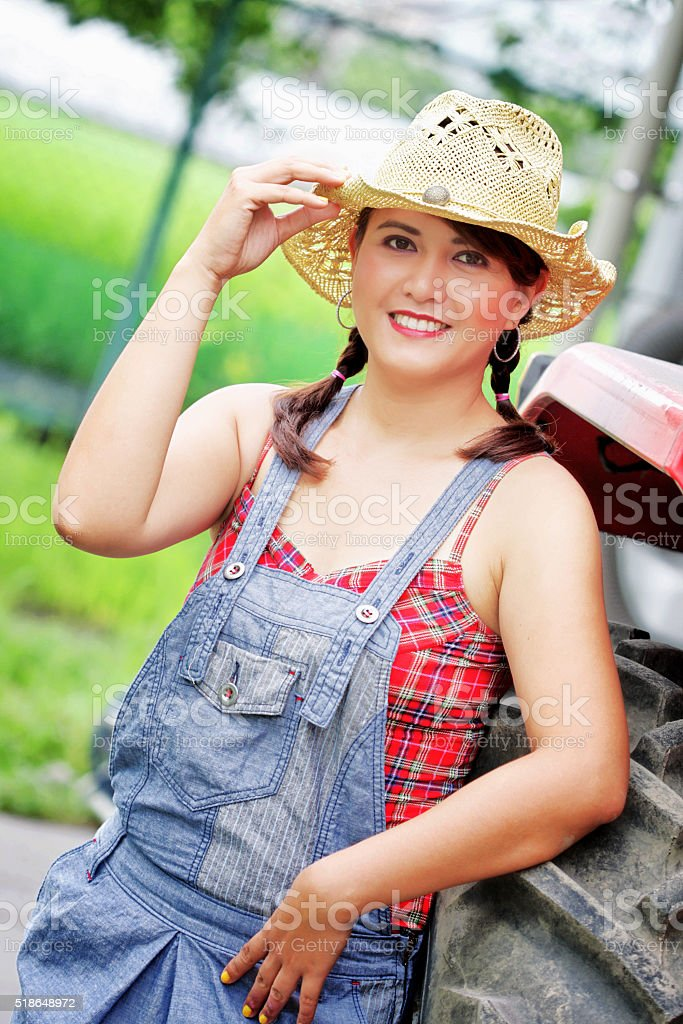 Portrait of country girl with tractor behind at sunrise stock photo
