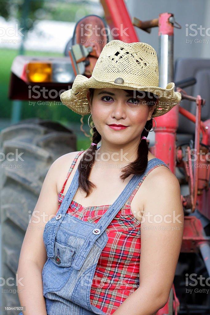 Porträt von Mädchen mit Traktor hinter Land Lizenzfreies stock-foto